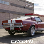 rear quarter of 1968 Shelby gt500 red with white stripes in front of crown concepts in tucson arizona
